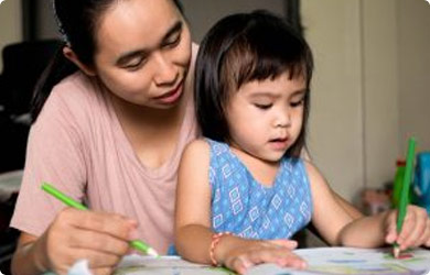 Mother teaching writing skills to her daughter